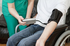 Blood pressure check for young adult in wheelchair Royalty Free Stock Photos