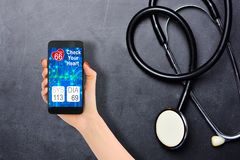 Blood pressure checking or tracking with smartphone and stethoscope on blackboard royalty free stock images