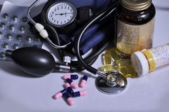 Blood pressure control. This picture represents a manometer to measure blood pressure and several pills and capsules adequate to control it Stock Photo