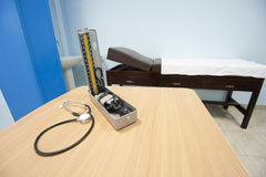 Blood pressure cuff and examination bench Royalty Free Stock Photo