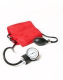Blood pressure cuff and gauge. A red blood pressure cuff and gauge royalty free stock images