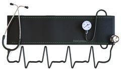 Blood pressure cuff with stethoscope in the shape of a heart waveform. Royalty Free Stock Photo