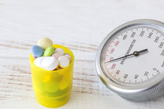 Blood pressure gauge with yellow pill box next to it, close up Royalty Free Stock Photos