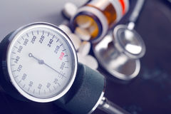 Blood pressure measuring instrument and pills. On a dark background Stock Images