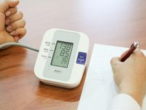 Blood pressure measuring and and taking notes. Blood pressure measuring and taking blood pressure and irregular heart beat pulse rate notes Health and Medical Royalty Free Stock Photo