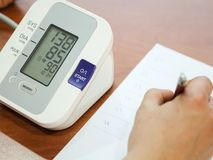 Blood pressure measuring and and taking notes. Blood pressure measuring and taking blood pressure and irregular heart beat pulse rate notes Health and Medical Royalty Free Stock Photos