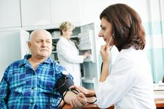 Blood pressure medic test. Doctor measuring blood pressure of patient by phonendoscope in clinic hospital Stock Images