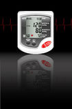 Blood pressure monitor. A digital blood pressure monitor against black with reflection on shiny surface. Heartbeat shown in red Royalty Free Stock Photo