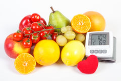 Blood pressure monitor and fruits with vegetables, healthy lifestyle. Blood pressure monitor with result of measurement and fresh fruits with vegetables, healthy Stock Photo