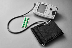 Blood pressure monitor tonometer with a pack of tablets. health care concept. royalty free stock photography