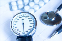 Blood pressure. Stethoscope, blood pressure monitor close up, pills and pen on electrocardiogram chart. Medical concept for cardiology, examination, screening Royalty Free Stock Image