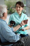 Blood pressure. Young pretty nurse checking the older man's blood pressure Stock Photography