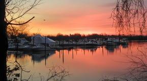 Blood Red Dawn at Marina. The sky glows orange over a tree shrouded marina Stock Photos