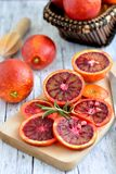 Blood red orange with slices. Bloody red oranges candied slices on a wooden cutting board royalty free stock image