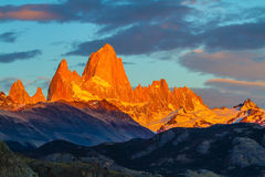 Blood-red sunset. Illuminates the top of impressive cliffs Fitz Roy. Fantastic Patagonia stock image