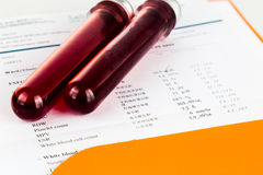 Blood sample in test tubes with health analysis screening report Stock Photo
