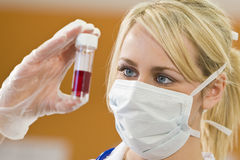 Blood Sample Too. A young female doctor/nurse looking at a blood sample Stock Photography