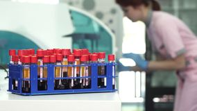 Blood samples in test tubes on the foreground copy space on the side. Blood samples in test tubes in a stack on the foreground female medical worker operating stock footage