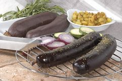 Blood Sausage. French boudin noir or blood sausage presented on grilled serving tray with other ingredients in background Stock Photo