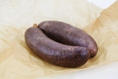 Blood sausage or black pudding on paper Royalty Free Stock Images