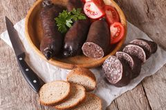 Blood sausages and vegetables on a table close-up. horizontal Stock Image
