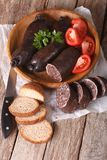 Blood sausages and vegetables on a table close-up. Vertical Royalty Free Stock Photography
