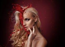 Blood splashing on a beuatiful woman`s face stock image