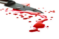 Blood splatter. Red blood splatter with kitchen knife in background, shallow DOF stock photos