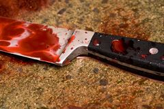 Blood stains. Close up of blood stained knife in pooling blood stock photos