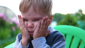 Summer evening time. A small child covers his face with his hands from mosquitoes. Blood-sucking insects. Blood-sucking insects. Summer evening time. A small stock footage