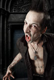 Blood sucking vampire. Photo of a male vampire with mouth open and fangs showing. Harsh lighting and heavily filtered for scarier feel Stock Images