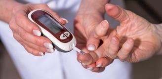 Blood sugar level checking. Nurse checking blood sugar level stock image