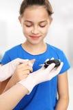 Blood sugar testing, child finger lancet punctures Royalty Free Stock Photos
