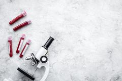Blood test concept. Blood samples near microscope on grey background top view copy space stock photo