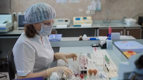 Blood test tubes being analyzed and interchanged by a laboratory worker. Work in the medical laboratory at the hospital stock footage
