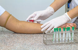 Blood test from venous vein  of patient by female doctor in whit Royalty Free Stock Image