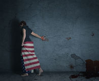 Blood trail. Young woman at a grey wall wearing american flag with a blood trail behind her Stock Images