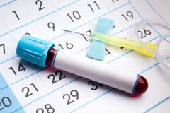 Blood tube and needle on the bottom of an appointment calendar Royalty Free Stock Images
