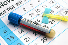 Blood tube and needle over a appointment calendar in workbench o. Blood sample tube and needle on the bottom of an appointment calendar in lab table / blood tube Stock Image