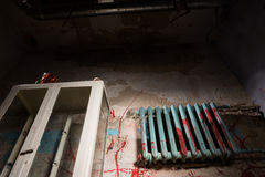 Bloodied battery near glass case in dimly lit basement Stock Photography