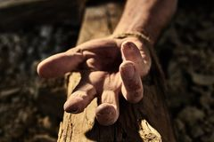 Bloodied hand with nail hole on a wooden cross stock image