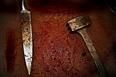 Bloodied metal hammer and knife Royalty Free Stock Photo