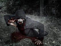 Bloodied zombie beklimt goed uit het riool stock afbeelding