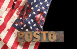 Bloodstains on USA flag with Boston word. Bloody American flag and the word Boston in old wood type on a black background Royalty Free Stock Photography