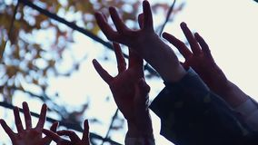Bloodthirsty creatures stretching hands to catch victim, zombie attack in city