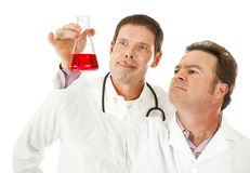 Bloodthirsty Doctor. Licks his lips as a colleague analyzes a blood sample.  Humorous image Royalty Free Stock Photo