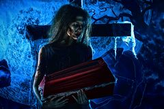 Distress. Bloodthirsty witch standing at the night cemetery and holding a coffin Royalty Free Stock Photography