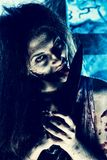 Bloodthirsty. Zombi with a knife standing at the night cemetery in the mist and moonlight Royalty Free Stock Photography