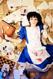 Bloody alice. Portrait of a young woman dressed as Alice in Wonderland, video game Royalty Free Stock Photos