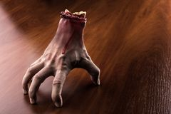 Bloody arm stands on the table Royalty Free Stock Image
